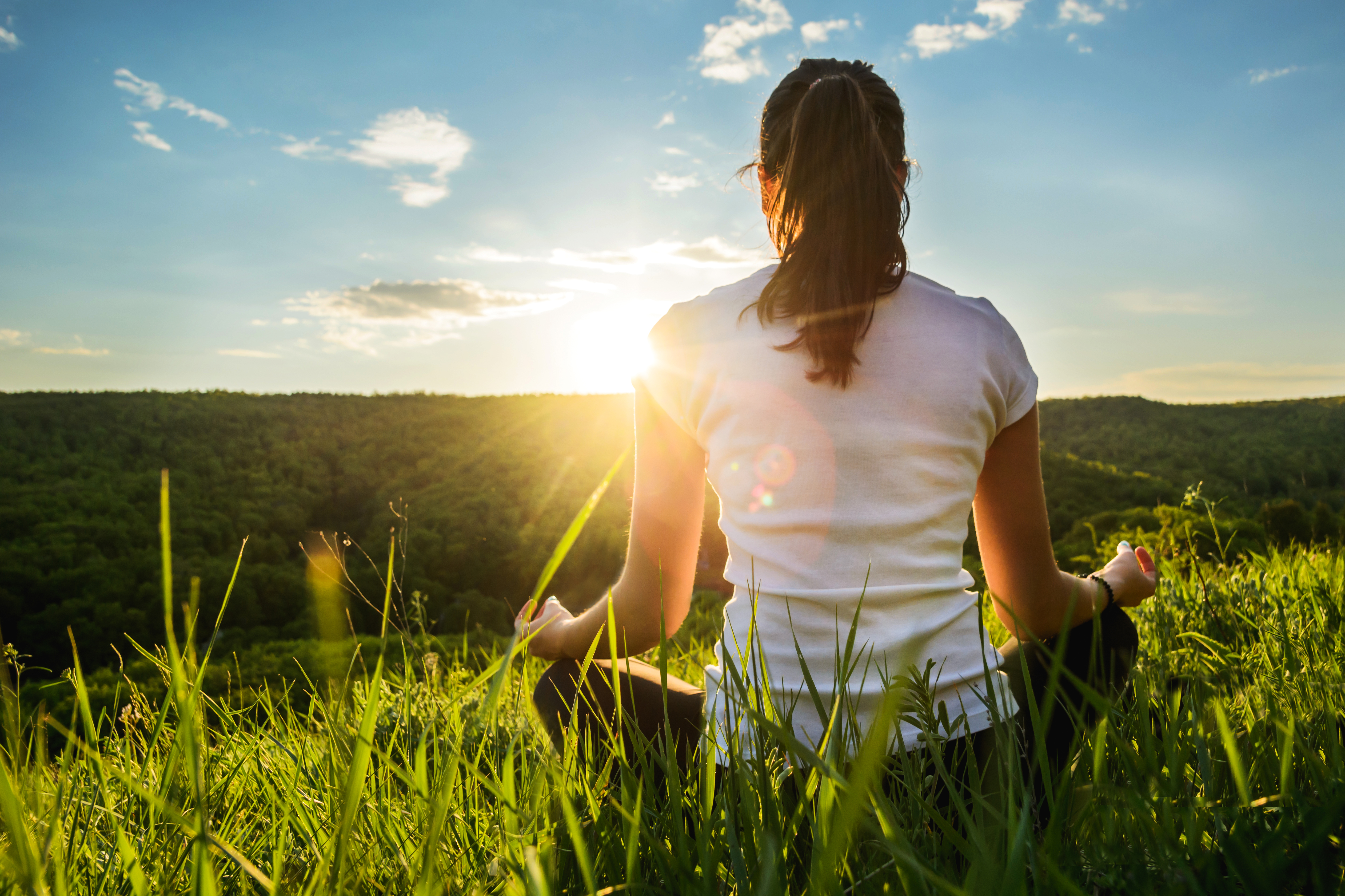 woman practices yoga on the hill during sunset