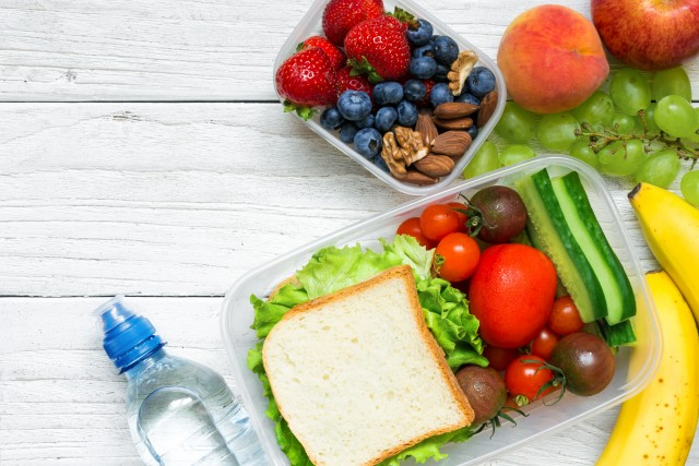 School lunch boxes with sandwich, fruits, vegetables and bottle of water and copy space. Top view